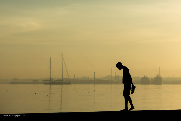 10 Things You Can Learn About Photography from Elliott Erwitt - silhouette of a man at sunset with boats