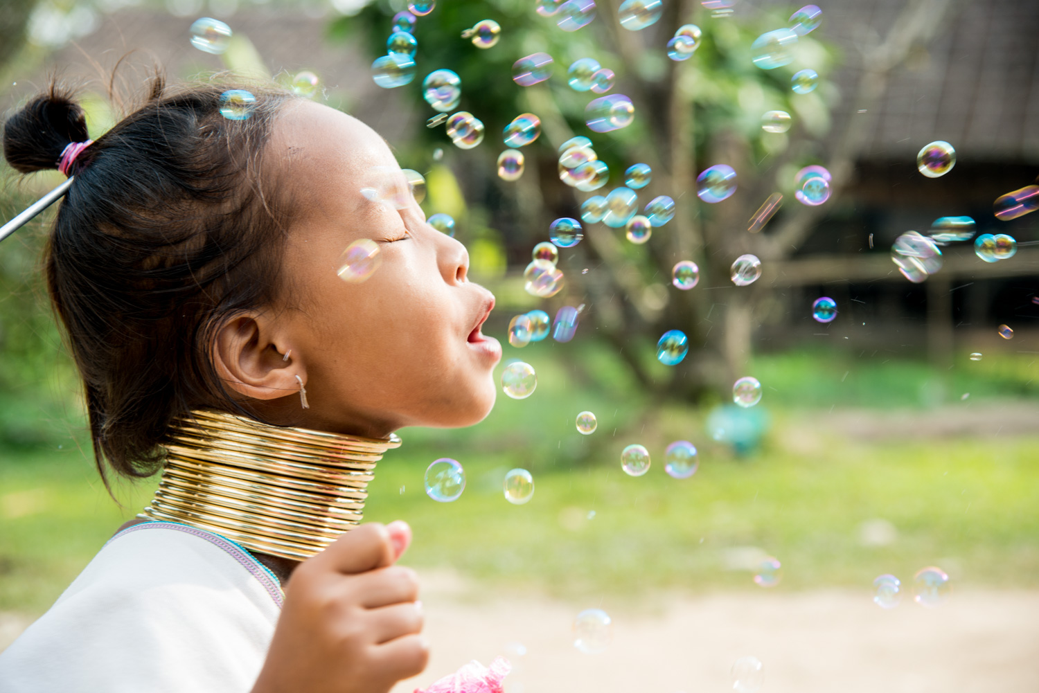 Kayan girl playing with bubbles. Photo by Kevin Landwer-Johan (copyright) - How to Avoid Distracting Backgrounds in Street Photography
