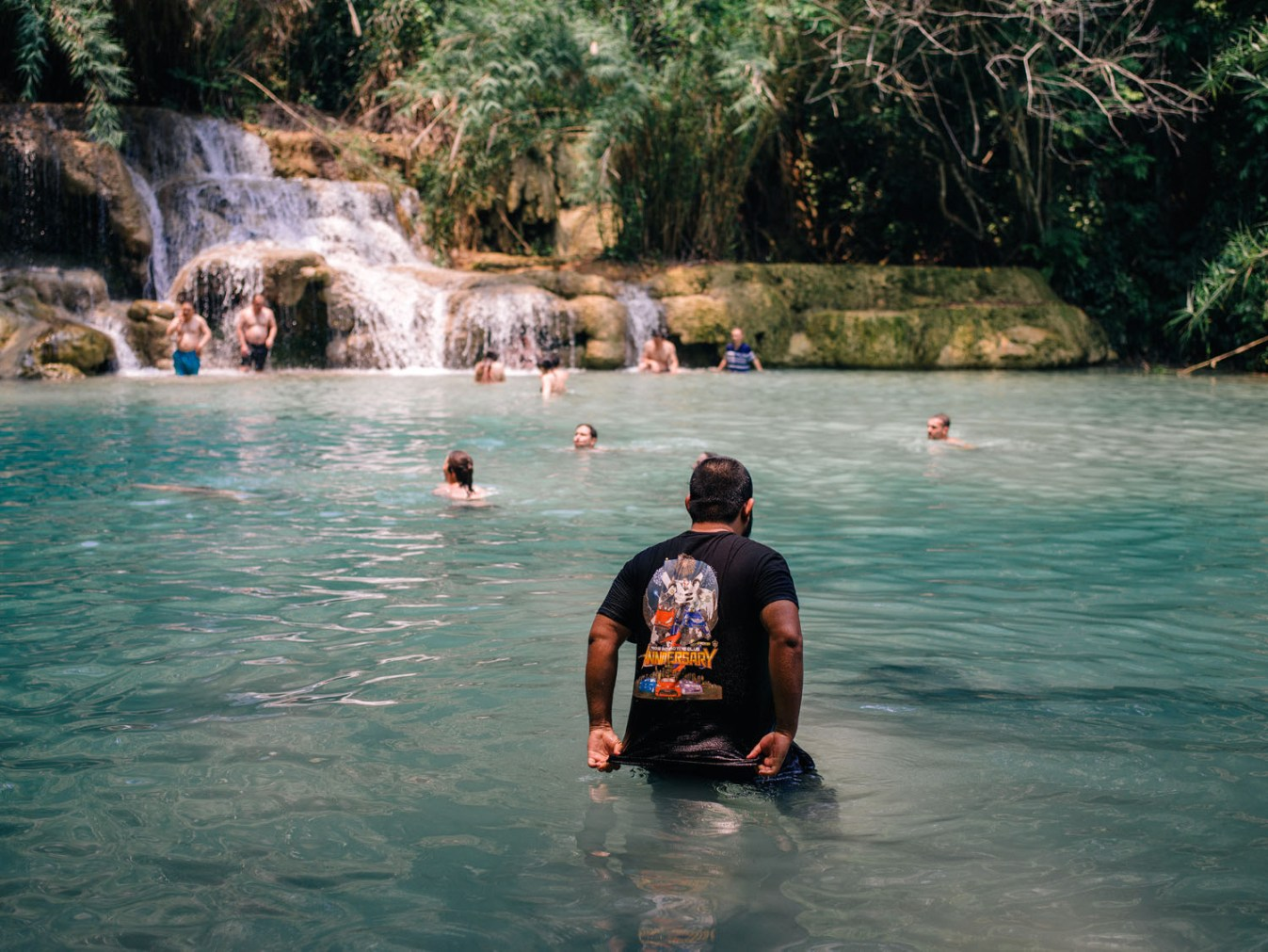 people in a pond by waterfall - How to Make Travel Photography Interesting Again