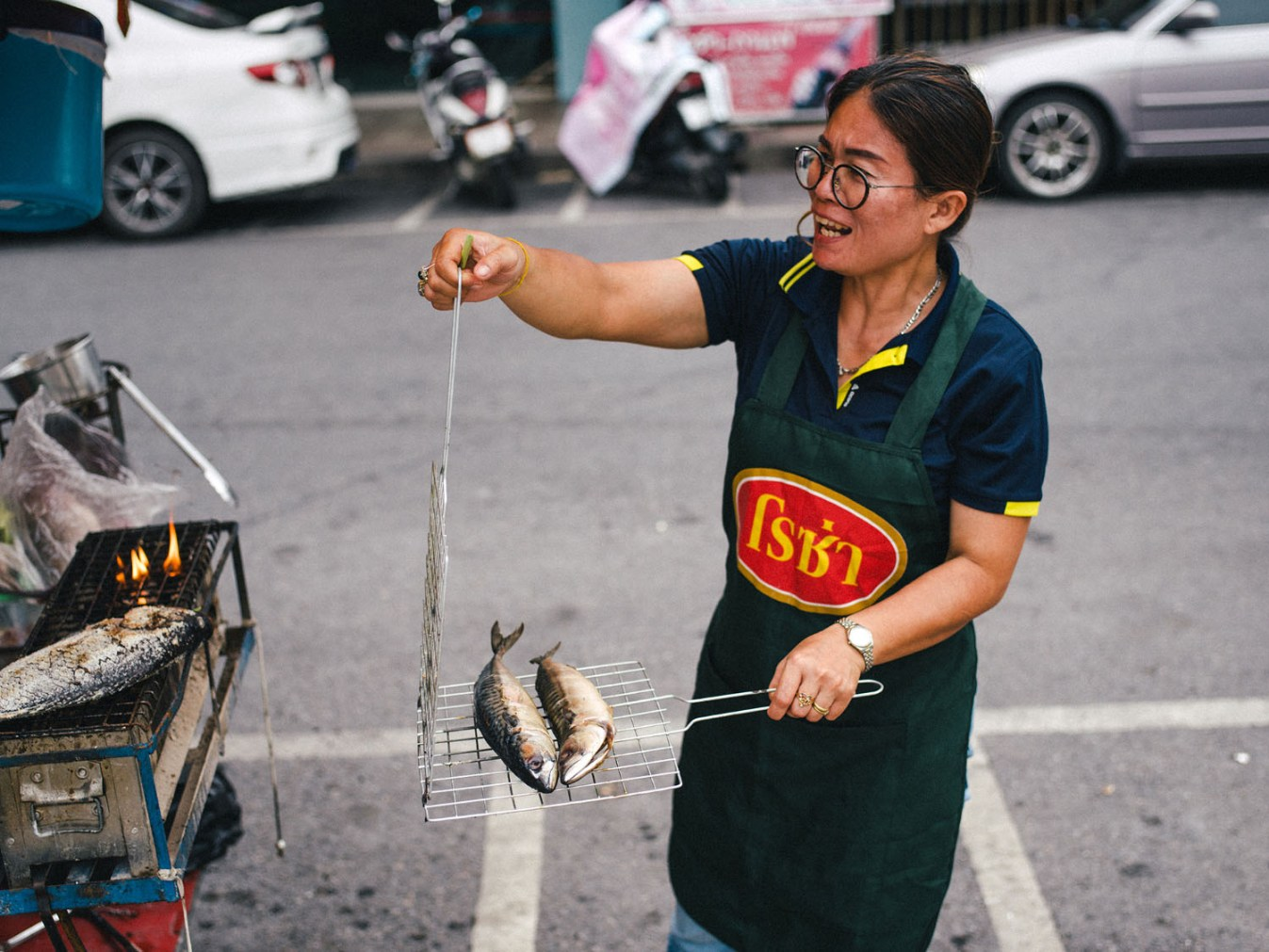 woman grilling fish on the street - https://digital-photography-school.com/top-street-travel-photography-tips-2017/