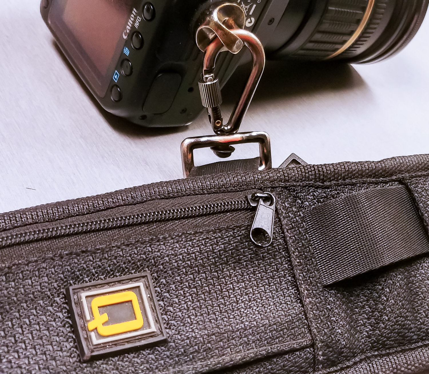 Image: A sling-style camera strap attached to the bottom tripod hole of a camera with a locking cara...