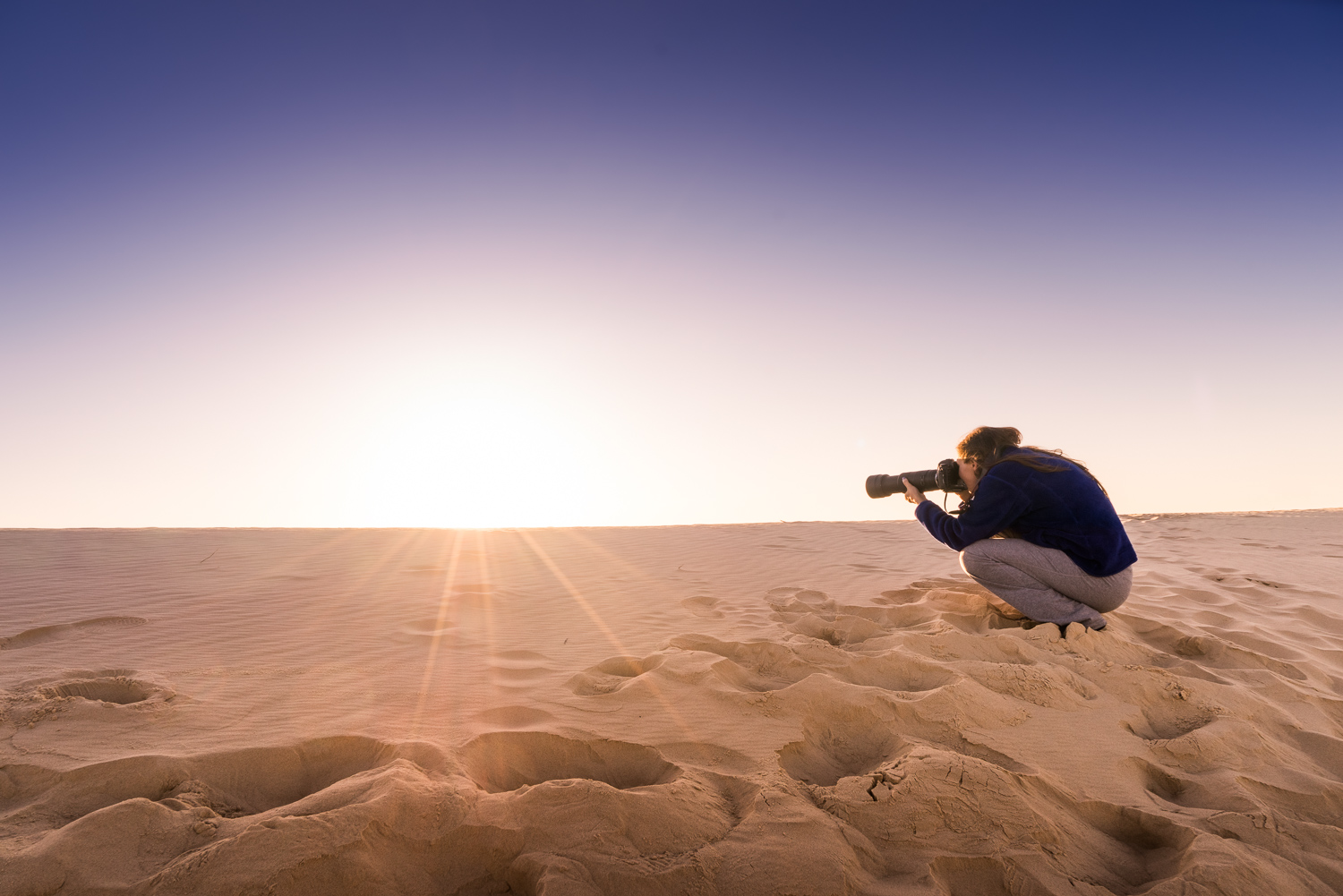 Woman crouching to make a photo in the desert