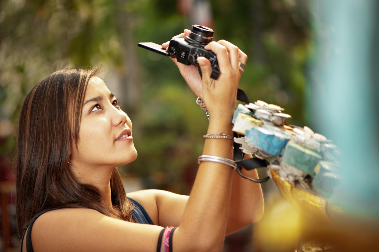 Woman taking a photograph manual exposure cheat sheet