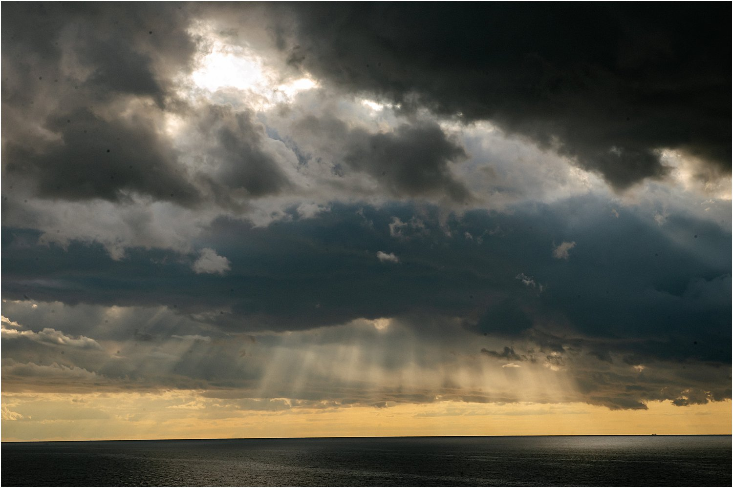 DPS photo by Lily Sawyer – Sun Rays shing through dark clouds over the water