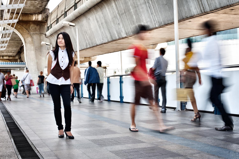 Mulher asiática em uma passarela da cidade com motion blur: erros comuns de câmera