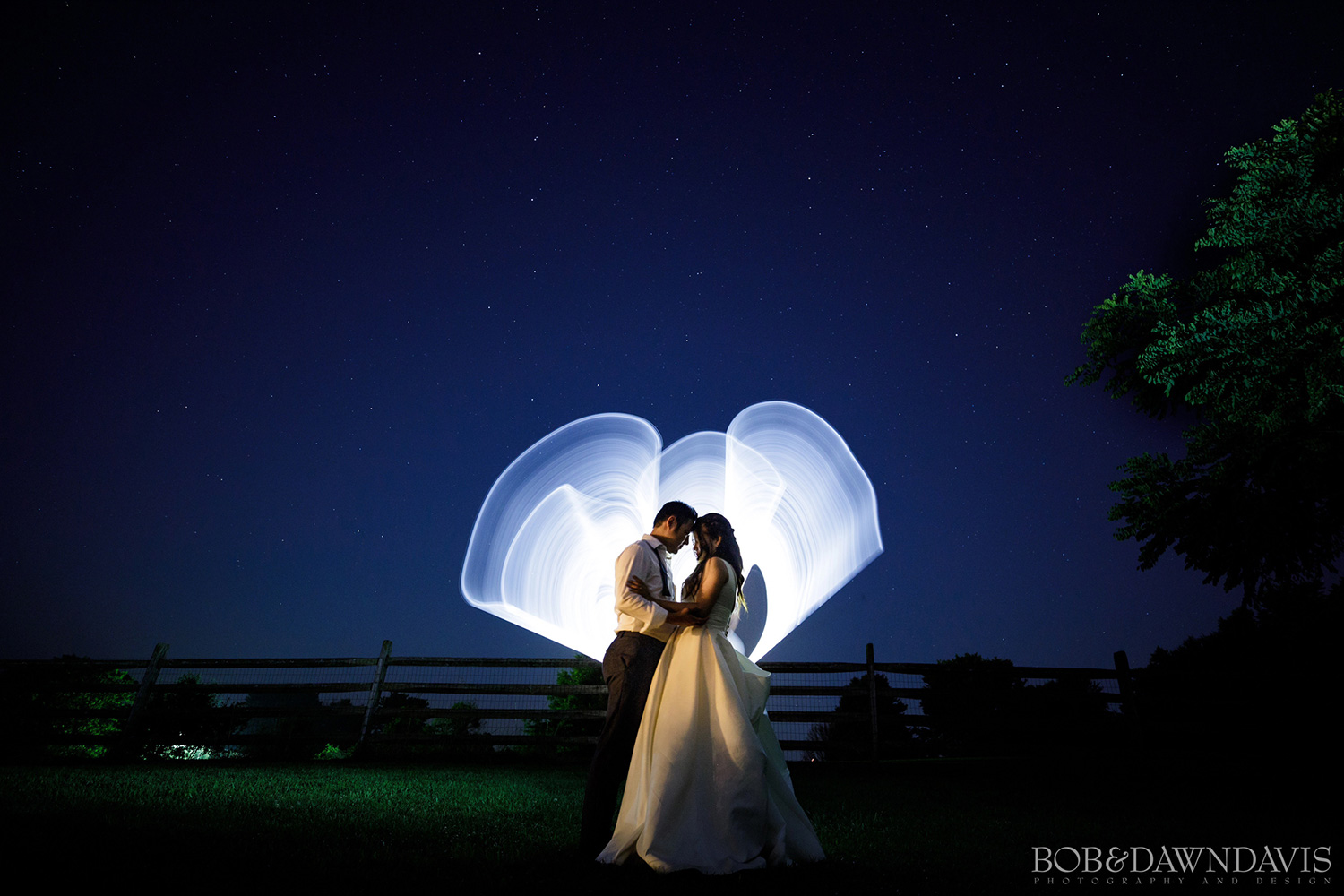 Light painting behind a bride and groom at a wedding in the evening. Photo by Photographers Bob and Dawn Davis