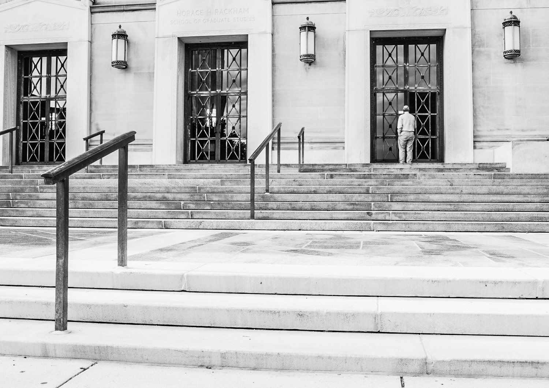 man walking through door street photography camera