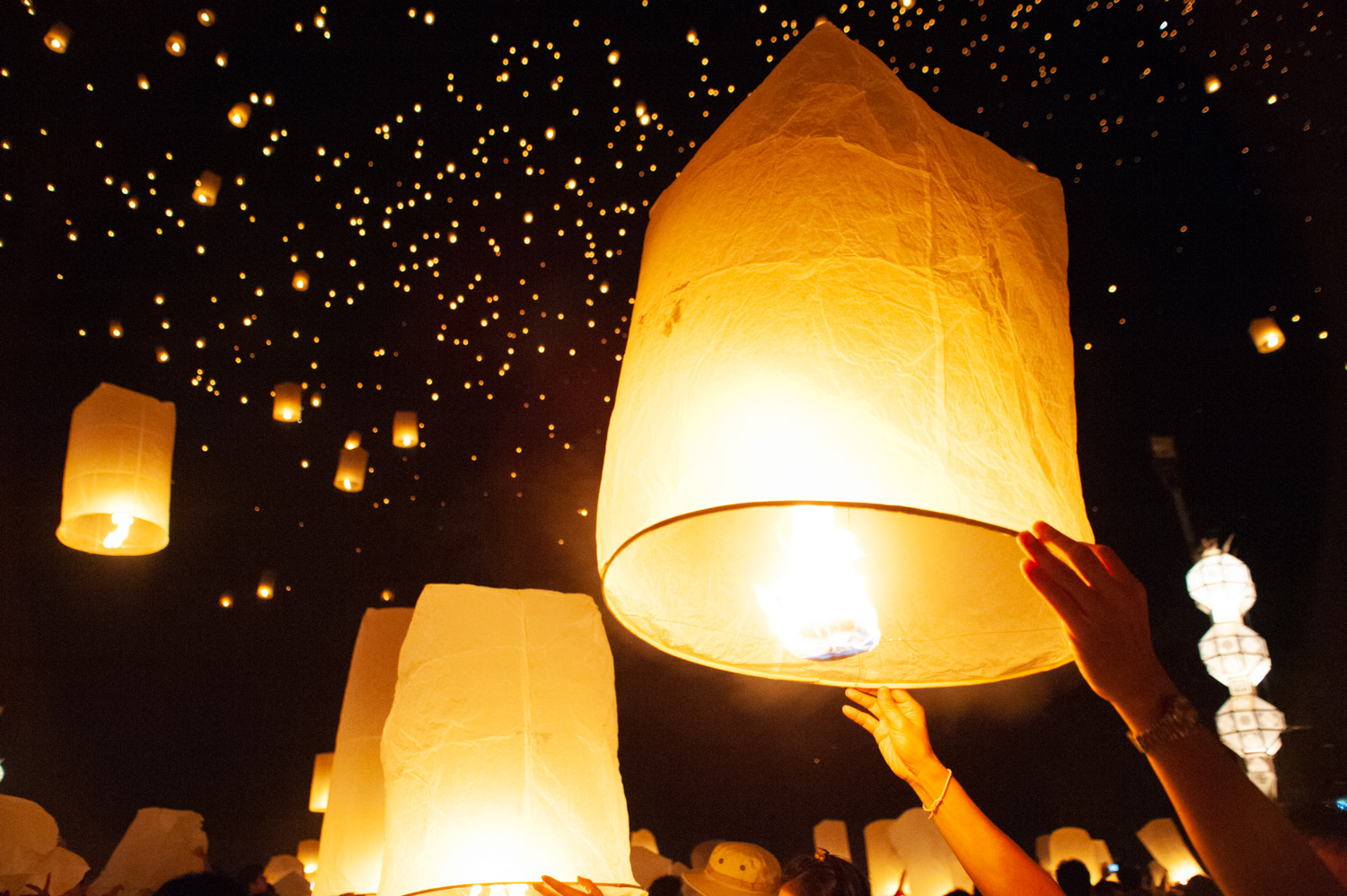 sky lanterns being released during the Loi Krathong festival in Thailand