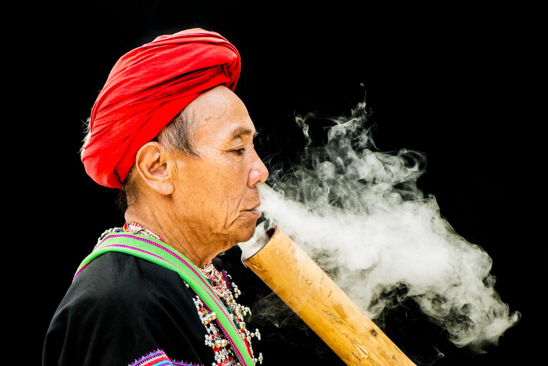 Homem Lahu fumando uma fotografia de cachimbo com intenção