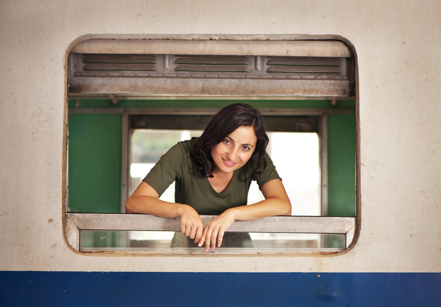 woman leaning on a window frame in a train for frame within a frame photography