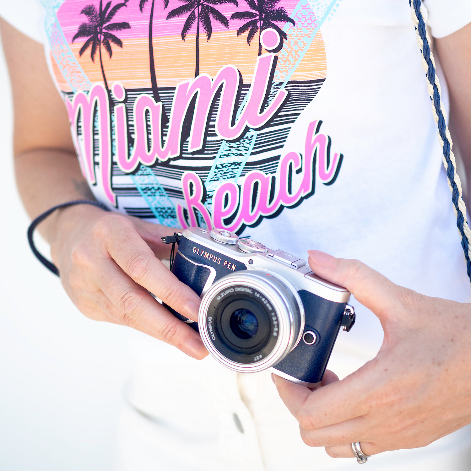 An Olympus camera held by a woman wearing a Miami T Shirt