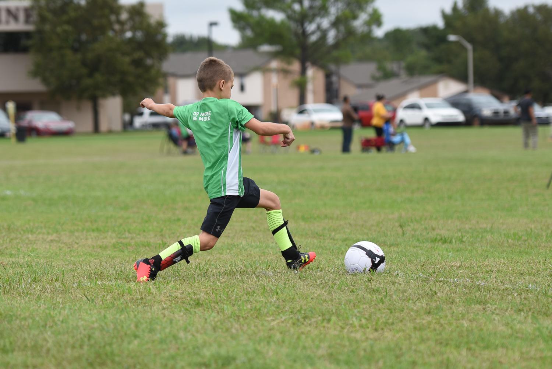 menino chutando uma bola de futebol