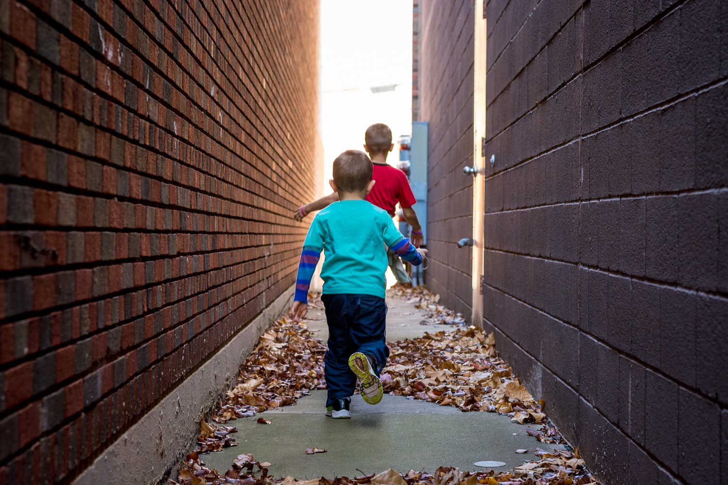 kids running in an alley with no color grading