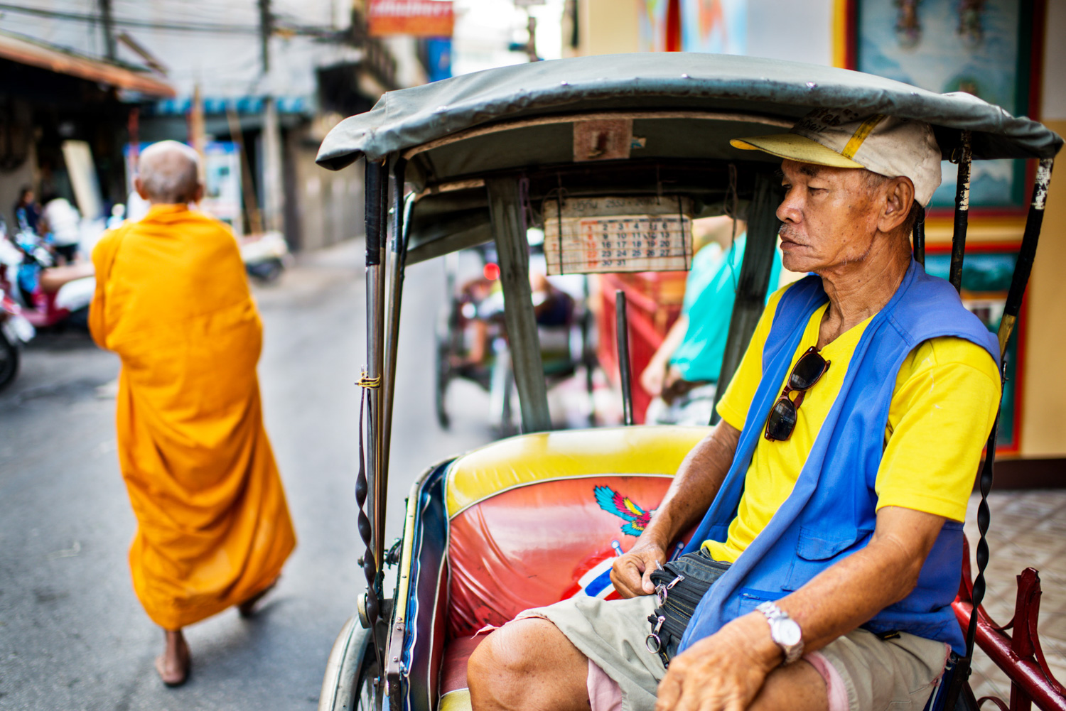 Tricycle taxi rider and a passing monk for 35mm street photography