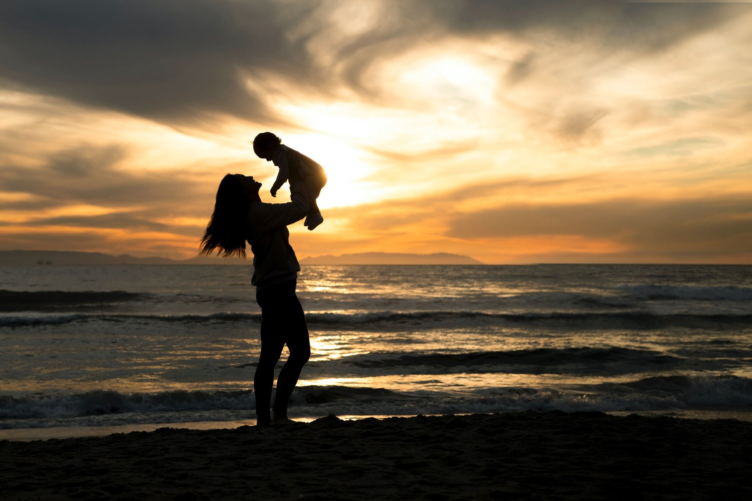 silhouette photography of a person holding a child