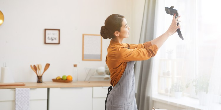 Side view portrait of beautiful young woman holding smartphone while filming story video for social media channel, copy space hp dengan fitur video 4k - HP dengan Fitur Video 4K yang cocok untuk vlog - 7 Rekomendasi HP dengan Fitur Video 4K Terbaik, Cocok Buat Nge-vlog