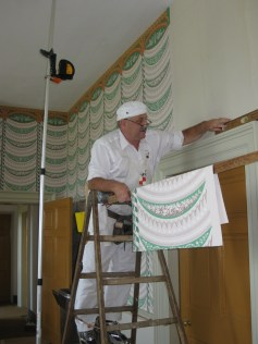Patrick Shields, of Shields Designs, hangs the wallpaper in the Madison's Dining Room.