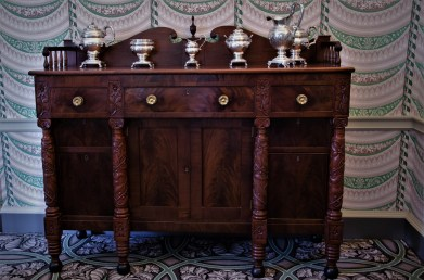 Classical mahogany sideboard with floral-carved columns with a swans-neck pedimented backboard.