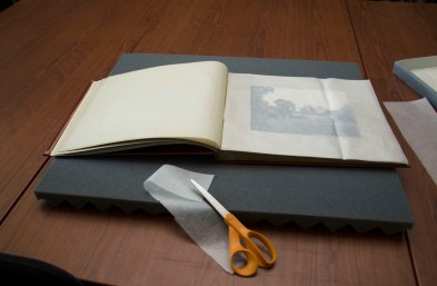 A duPont scrapbook is prepared for storage.