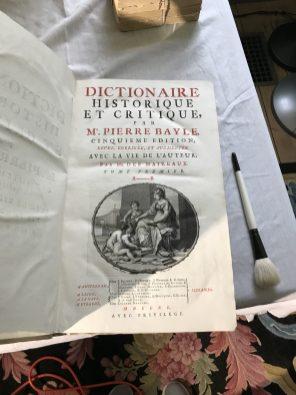 """A copy of """"Dictionaire Historique et Critque"""" being dusted."""