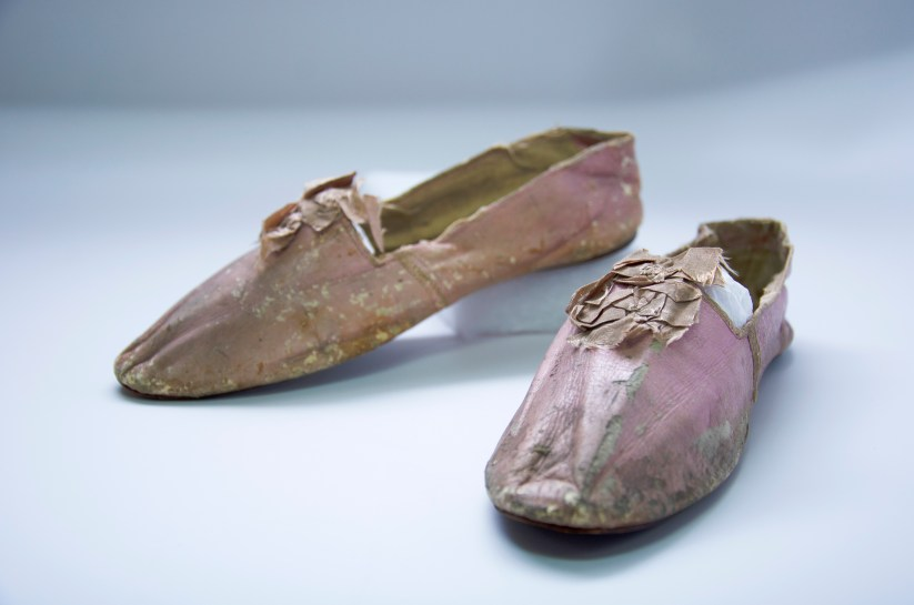 A pair of ealy 19th century women's pink leather slippers, featuring silk bows. Possible Dolley Madison provenance.