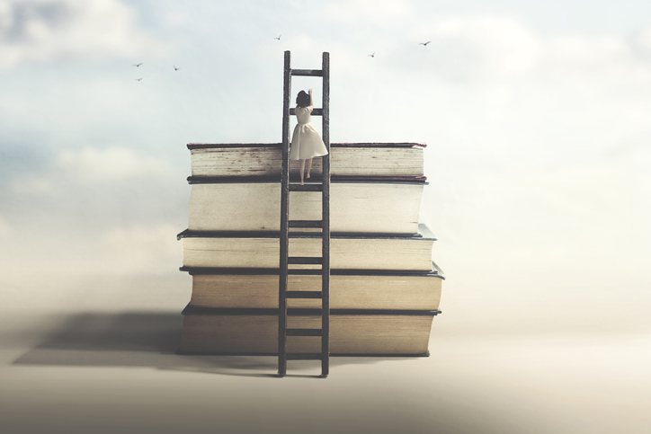 Woman climbing up ladder to reach the top of a stack of boocks