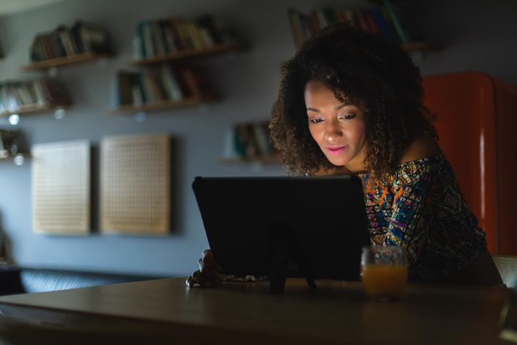 Woman at home using digital tablet at night