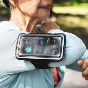 Woman runner with smartphone strapped to arm