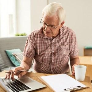 Man using laptop to work on finances
