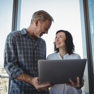 Man and woman having a discussion holding Windows laptop