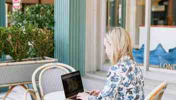 Blonde website designer sitting at cafe table outdoors working on her laptop in blue patterned blazer