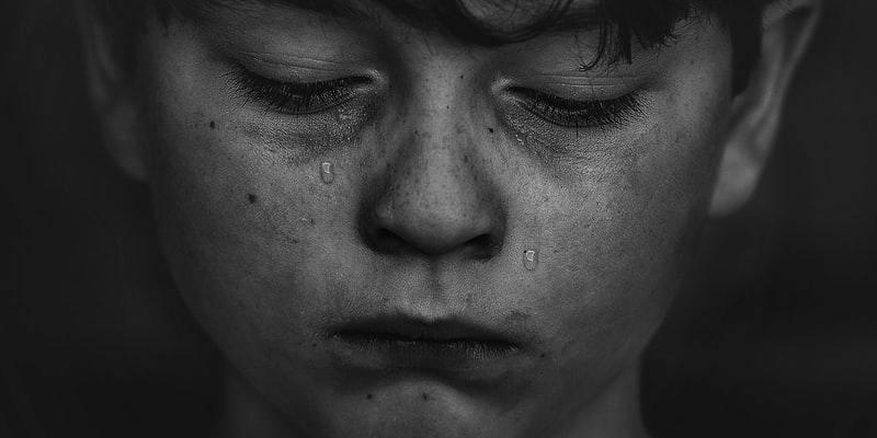 Un enfant qui coule des larmes, les yeux fermés