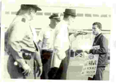Three policemen, two uniformed and one in plain clothes, speak to a young man - Jerry Gross - holding a protest sign