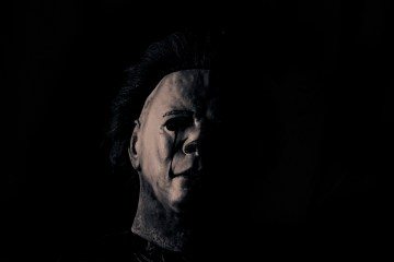 A dark image with the white mask of Halloween main character, Michael Myers