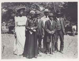 Two African American women dressed in formal dresses and hats and four African American men, wearing hats and suits, pose for the camera outside in a field with trees in the background