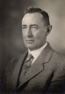 A black and white photograph of a white man in a gray suit, looking rather stern