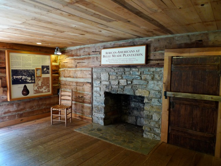 A large wood paneled room with a large stone fireplace with a wooden chair next to it