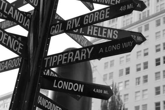 "A large street sign with many arrows, one reading ""London"" and another reading ""Tipperary - A Long Way!"""