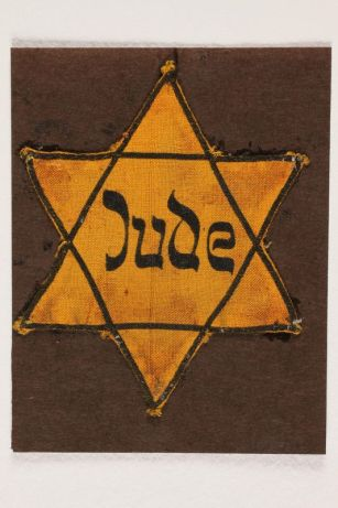 "W yellow Star of David with the word ""JUDE"" in the middle"