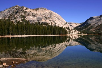 a panoramic photograph of a lake framed by mountains and pine trees