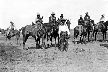 a black and white photograph of black cowboys on horseback