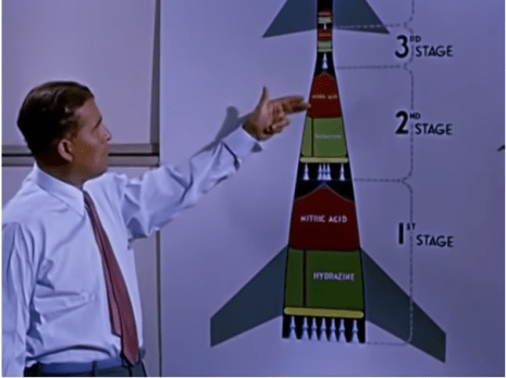 a color still from a video depicting Werhner von Braun pointing to a illustration of a rocket