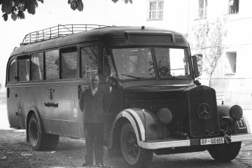 A man poses in front of a gray gekrat bus