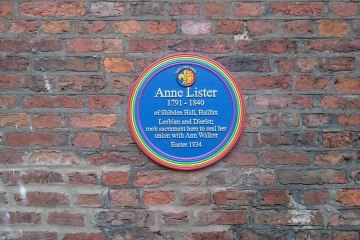 "The blue plaque has a rainbow border and is inscribed: ""Anne Lister 1791-1840 of Shibden Hall, Halifax. Lesbian and Diarist; took sacrament here to seal her union with Ann Walker Easter 1834"""
