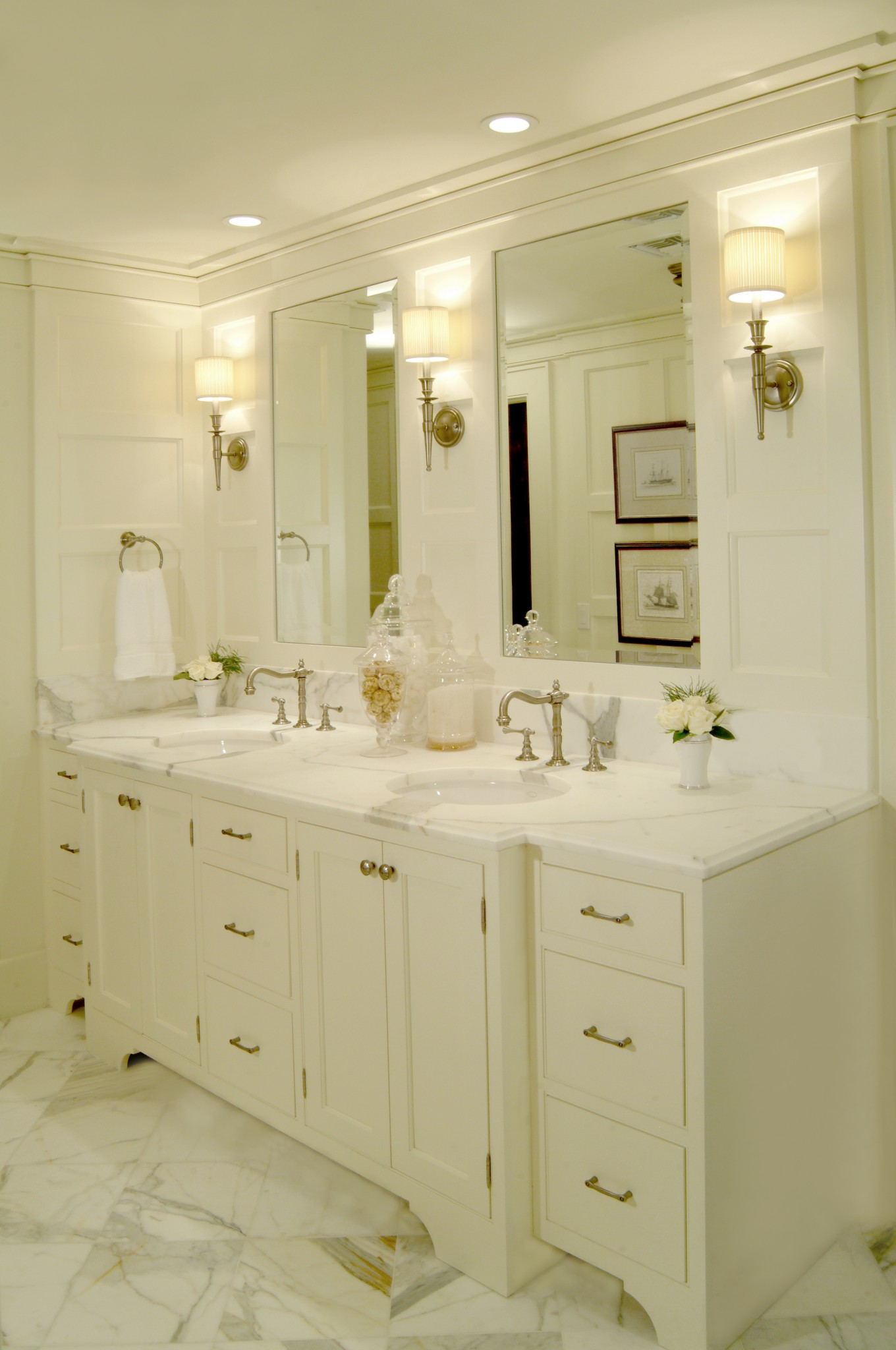 Master bathroom double sink vanity with marble floor tile and counter top. White painted wood wall paneling, recessed lighting and sconces for layered lighting plan