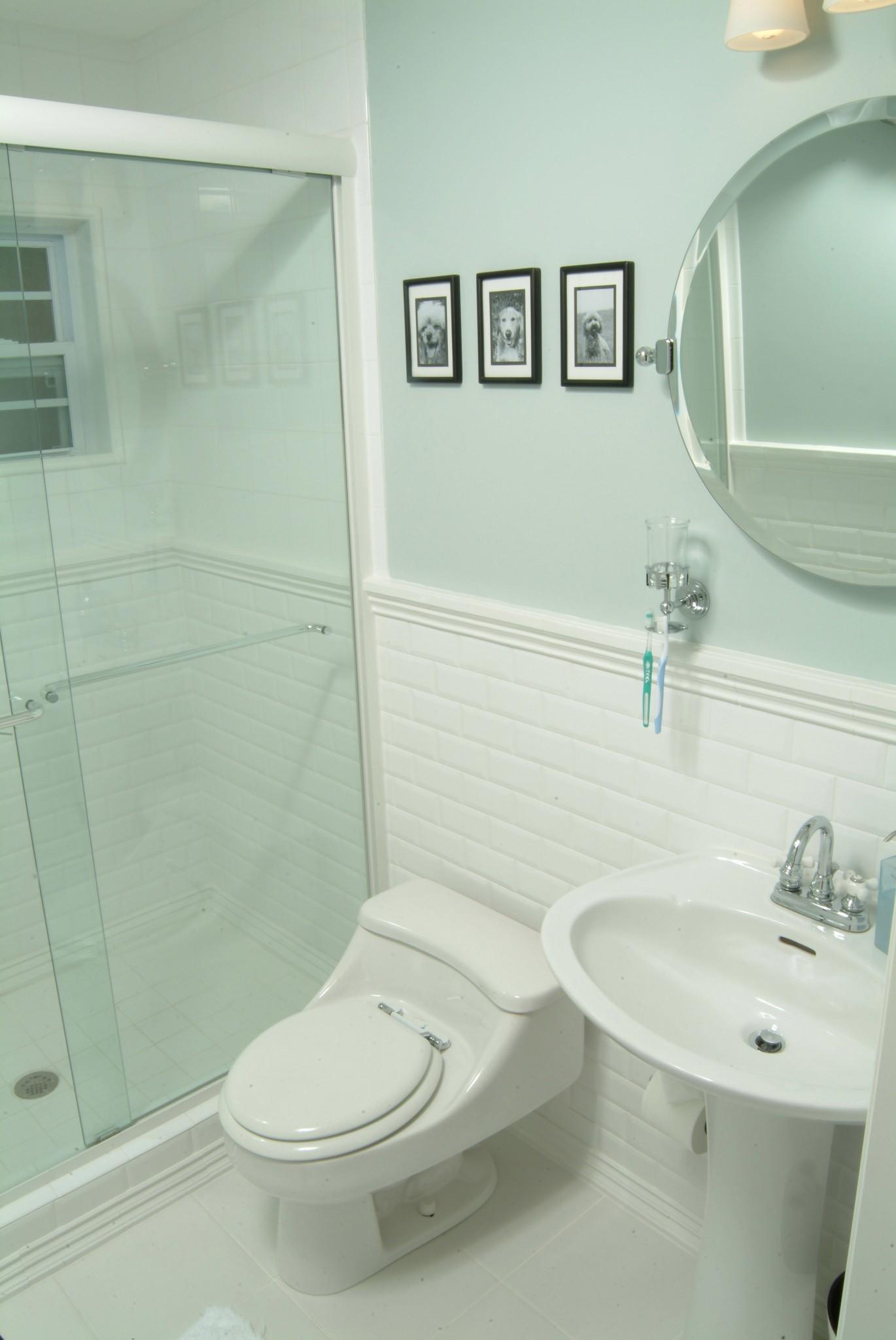 transitional guest hallway bathroom with white subway tile wainscot, light blue walls, pedestal ADA sink , tilt mirror, chrome fixtures, glass shower enclosure, and layered lighting plan
