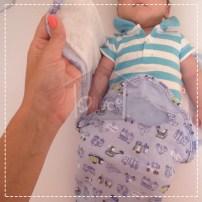 Coloque o bracinho do bebê na lateral ou cruzado sobre o peito e passe a lateral do SwaddleMe sobre o bebê