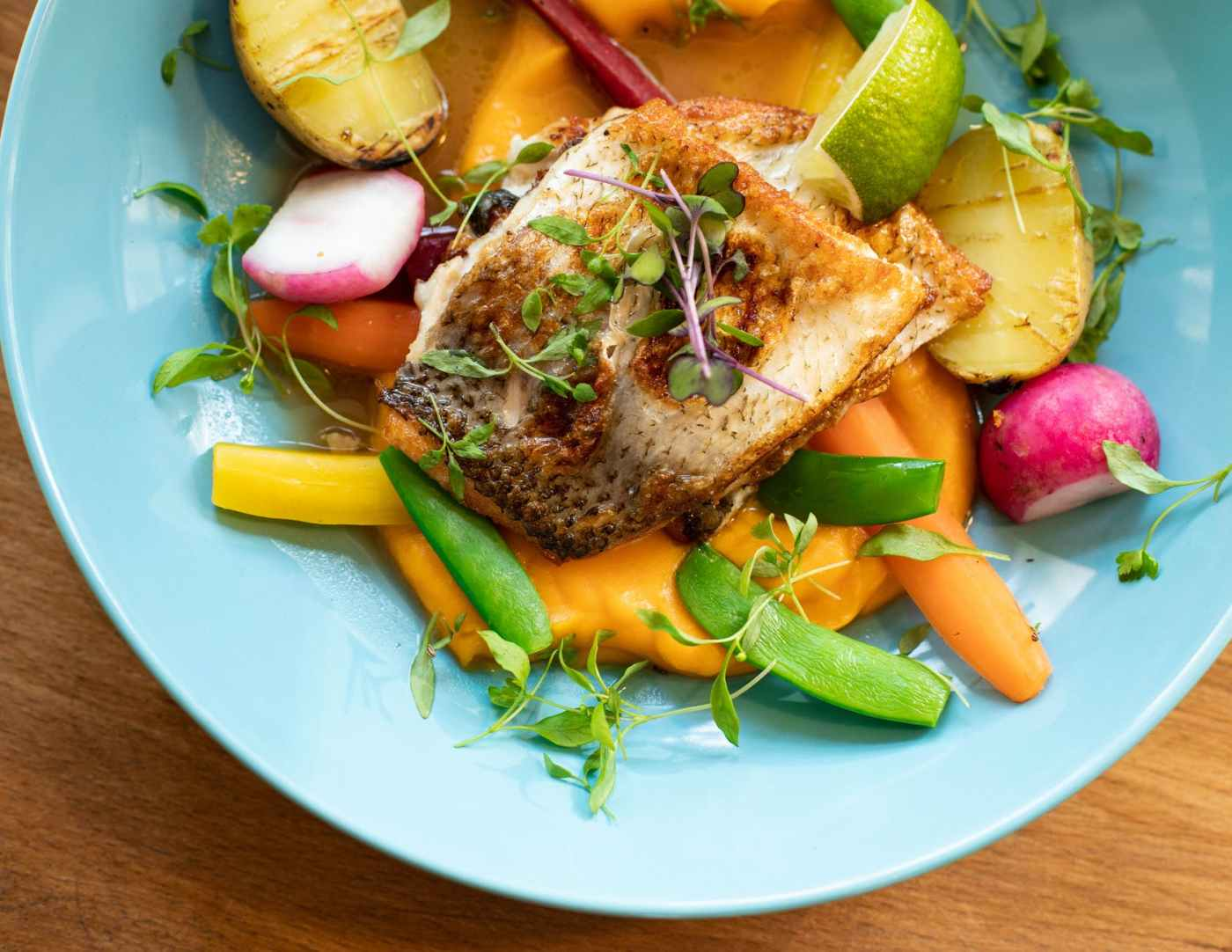 fried fish with vegetables dish on teal plate