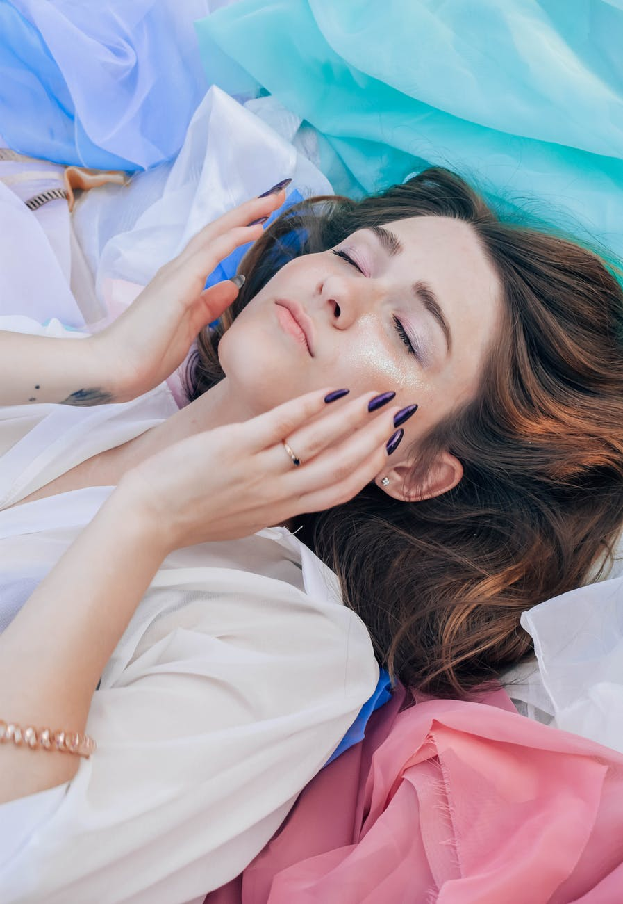 woman in white top lying on assorted color textiles