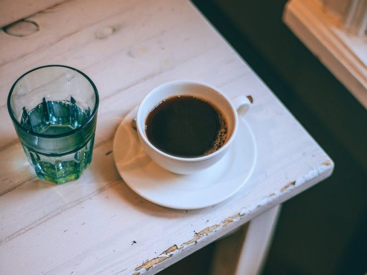 cup of espresso on wooden table at home